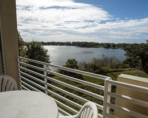 A balcony with patio furniture alongside the lake.