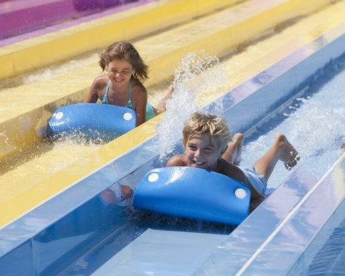 A view of two kids water sliding.