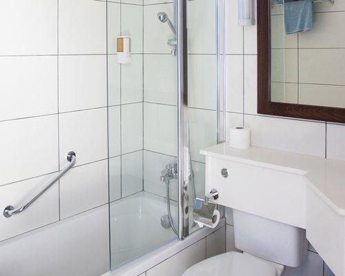 A bathroom with a bathtub shower and mirror.