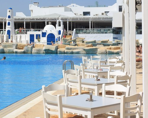 An outdoor swimming pool with multiple patio tables.