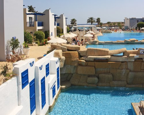 An outdoor swimming pool and sunshades alongside the resort unit.