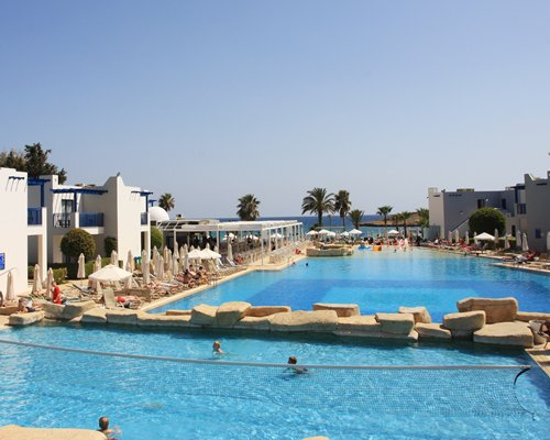 View of outdoor swimming pools with sunshades and chaise lounge chairs alongside the resort units.