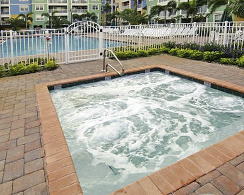 Mizner Place with outdoor swimming pool chaise lounge chairs and palm trees.