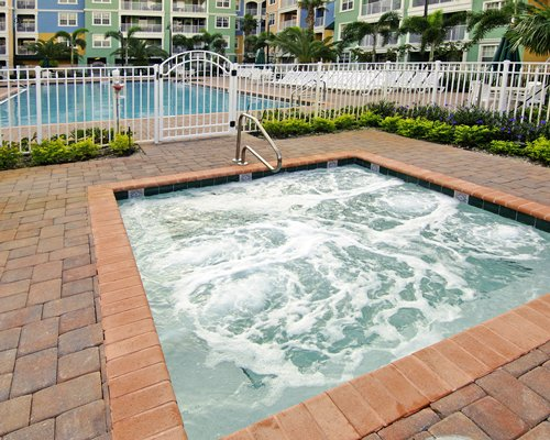 An outdoor hot tub alongside the swimming pool.