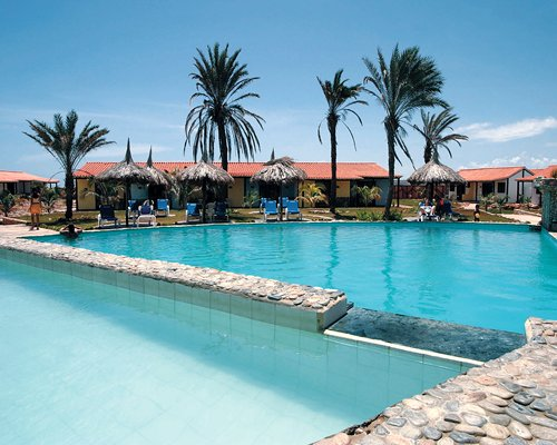 An outdoor swimming pool with chaise lounge chairs and thatched sunshades alongside the resort.