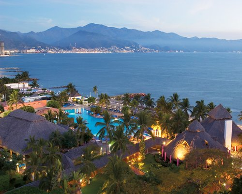 Club Melia at Melia Puerto Vallarta with outdoor swimming pool and palm trees alongside the ocean.