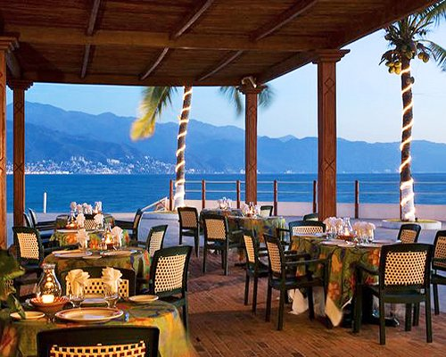 An outdoor fine dining restaurant with the a waterfront view.