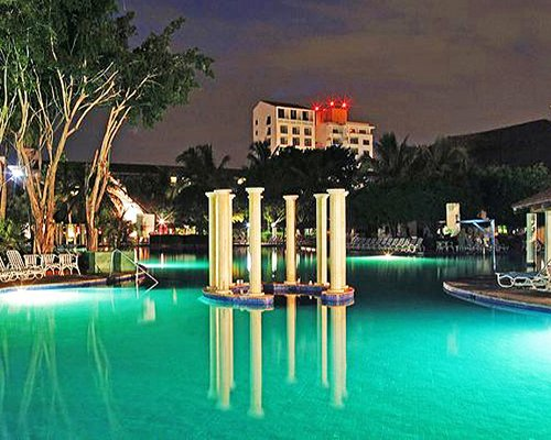 An outdoor swimming pool alongside the resort at night.