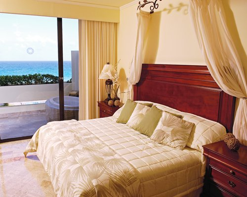 A well furnished bedroom with king bed balcony and sea view.