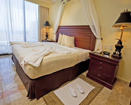 A well furnished bedroom with king bed and balcony.