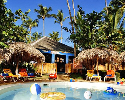 Outdoor kiddie pool with chaise lounge chairs thatched sunshades and palm trees.