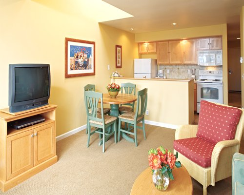 An open plan living room with a television dining and kitchen area.