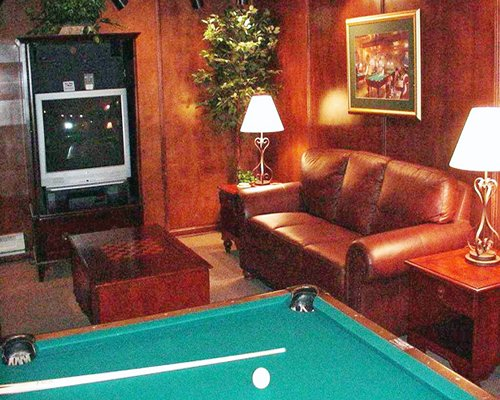 An indoor recreational room with ping pong table and television.