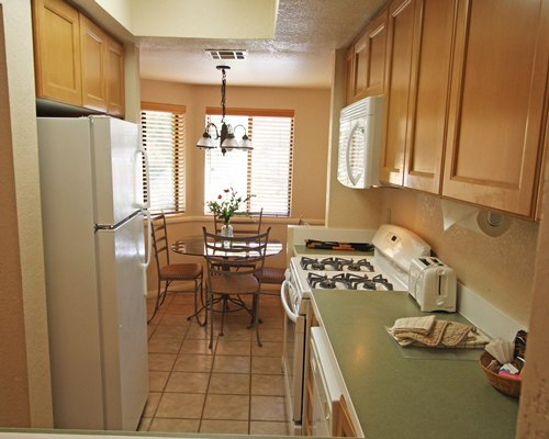 A well equipped kitchen with a dining area and an outside view.