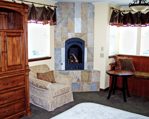 A well furnished living room with a fire in the fireplace and outside view.