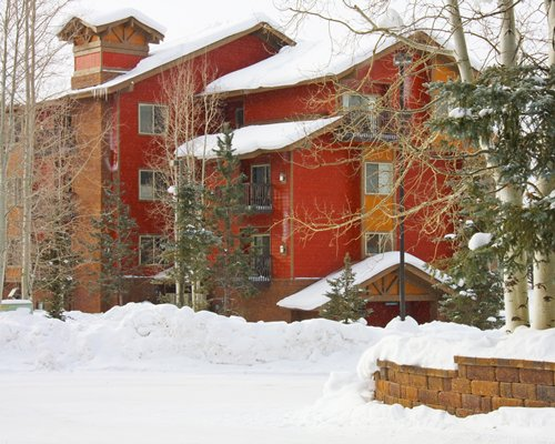Exterior view of a unit with balcony covered with snow during winter.