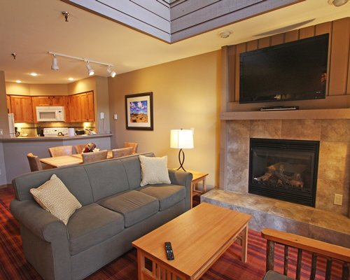 An open plan living room with a television fireplace dining and kitchen area.