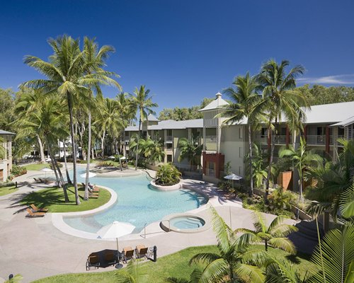 An aerial view of the outdoor swimming pool with chaise lounge chairs alongside the resort.