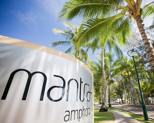 Signboard of Mantra Amphora resort alongside coconut trees.
