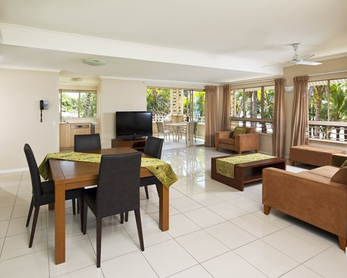 A well furnished living room with a dining area television open plan kitchen and outdoor view.