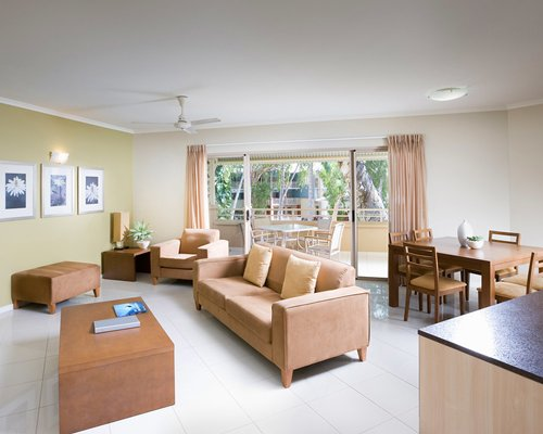 An open plan living and dining area with a balcony and patio furniture.