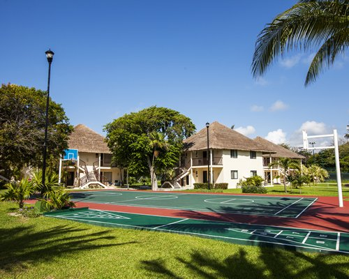 An exterior with outdoor basketball court and shuffleboard in foreground.