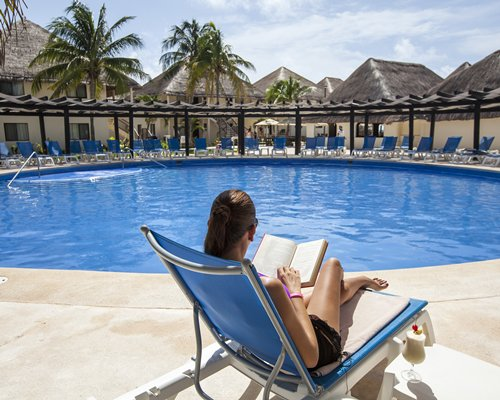 A resort exterior with swimming pool area chaise lounge chairs and woman reading.