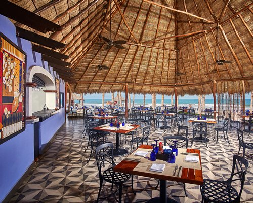 An open air restaurant with multiple tables ocean view and high thatched ceiling.