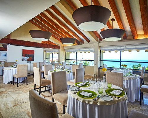 A fine dining restaurant interior with multiple dining tables windows and ocean view.