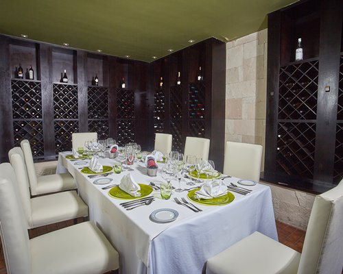 A fine dining restaurant with a large dining table and wall wine racks.