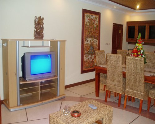 A well furnished living room with television and dining area.
