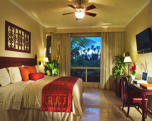 A well furnished bedroom with a king bed television and outdoor view.