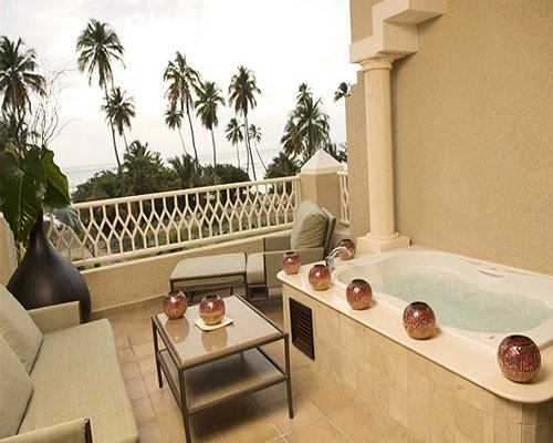 A hot tub in the balcony with patio furniture and chaise lounge chairs.