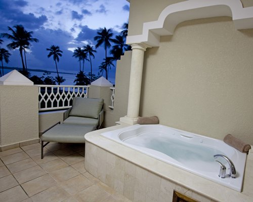 Balcony with bathtub and chaise lounge chair at dusk.