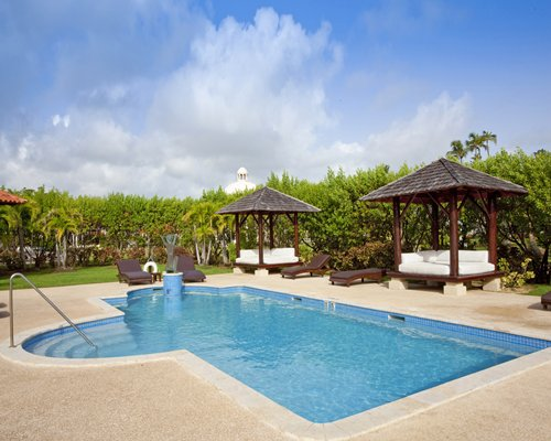Outdoor swimming pool with chaise lounge chairs and beach beds .