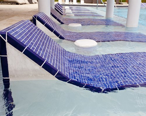 A view of in pool chaise lounge chairs.