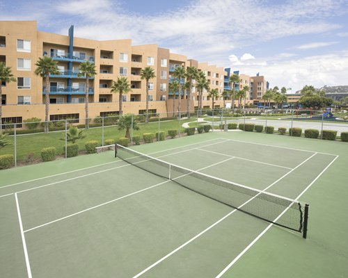 Outdoor recreation area with tennis court alongside multiple balconies.