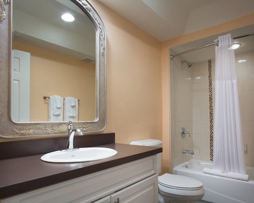 A bathroom with a bathtub shower and single sink vanity.