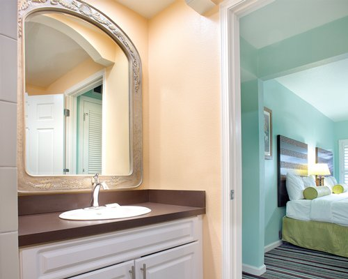 A sink and mirror alongside the bedroom.