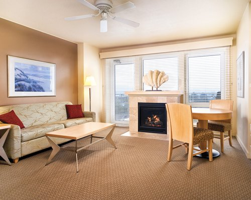 A well furnished living room with a fire in the fireplace dining table and outside view.