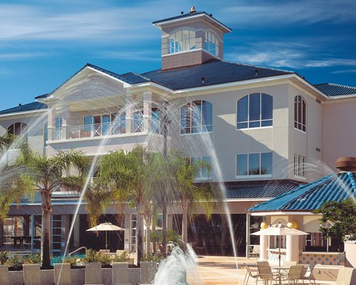 An exterior view of The Fountains resort with a sprinkler.