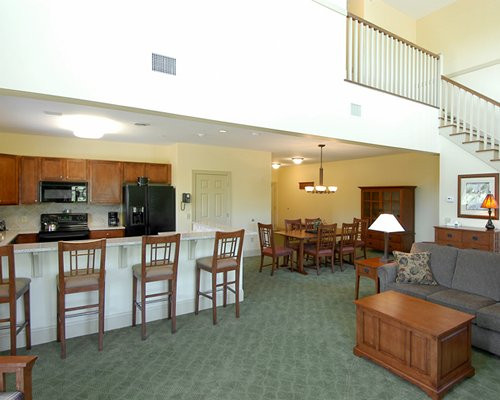 A well furnished living area alongside kitchen with a breakfast bar and the dining area.