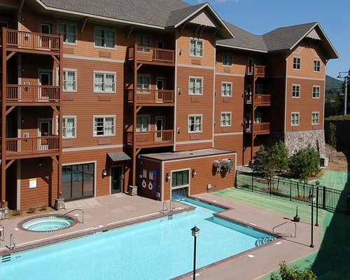 Exterior view of Kaatskill Mountain Club with multiple balconies outdoor swimming pool and hot tub.