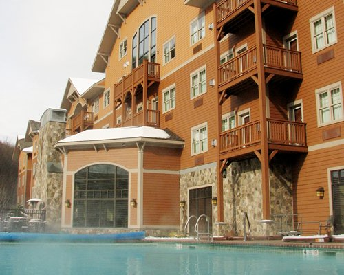 An outdoor swimming pool alongside multi story resort units.