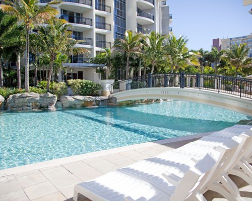 Large outdoor swimming pool with a bridge chaise lounge chairs and palm trees alongside the unit.