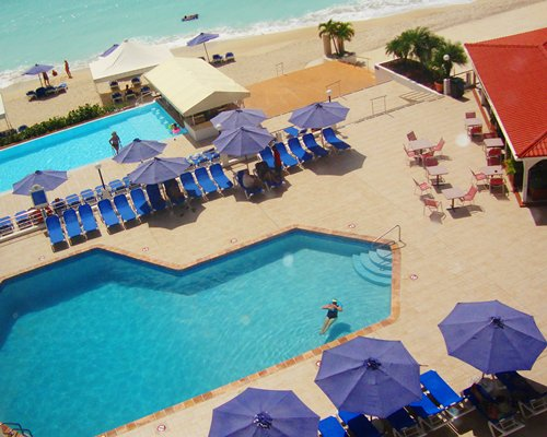 An aerial view of two outdoor swimming pools with sunshades chaise lounge chairs and dining alongside the beach.