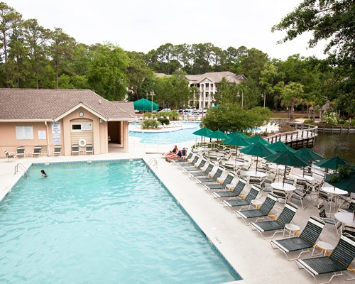 An outdoor swimming pool with sunshades and chaise lounge chairs alongside the resort units.