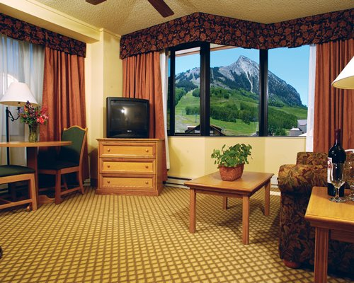 A well furnished living room with dining area television and outside view.