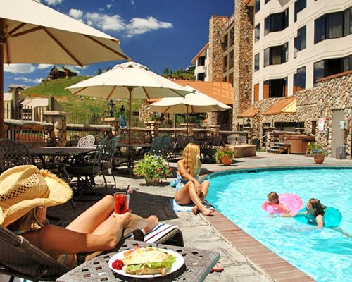 People relaxing at the outdoor swimming pool at Grand Lodge Crested Butte.