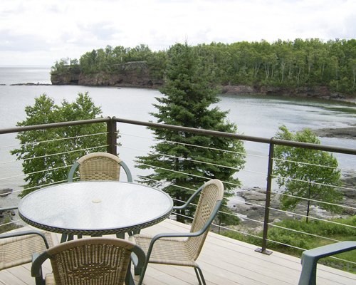 Balcony with dining alongside the lake with wooded area.